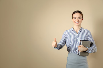 Portrait of young female teacher on beige background. Space for text