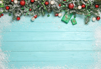 Flat lay composition with fir branches, Christmas decoration and snow on light blue wooden background. Space for text