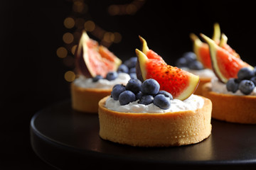 Tarts with blueberries and figs on black table against dark background, closeup. Delicious pastries