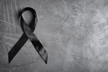 Black ribbon with space for text on grey stone background, top view. Funeral symbol