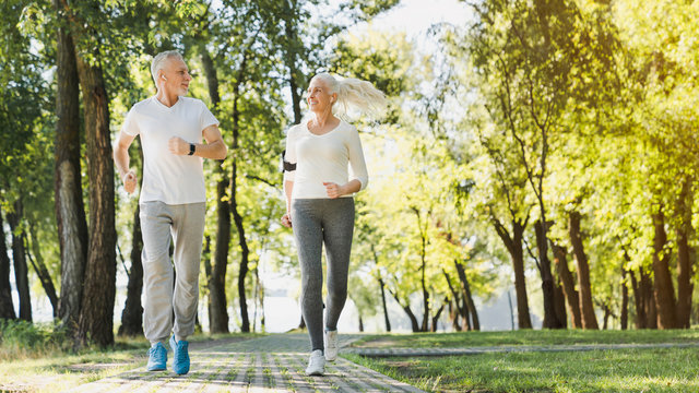 Full length of healthy mature couple jogging in park at early morning