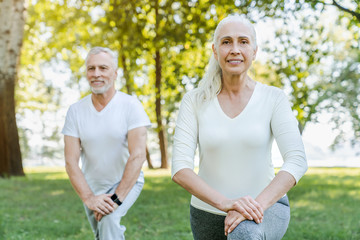 Mature couple stretching together in park outdoors before yoga and fitness exercises