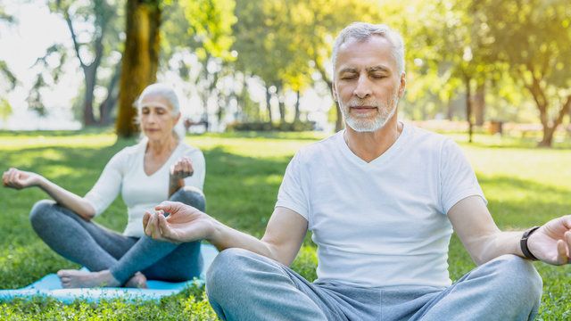 Yoga at park. Senior couple sitting in lotus pose on green grass in calm and meditation