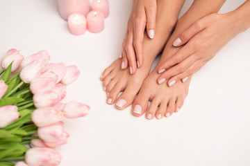 Photo sur Plexiglas Pedicure The picture of female legs and hands after pedicure and manicure. Legs are surrounded by pink tulips and candles.