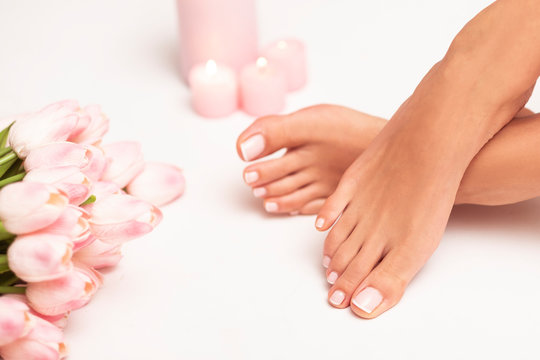The picture of female legs and hands after pedicure and manicure. Legs are surrounded by pink tulips and candles.