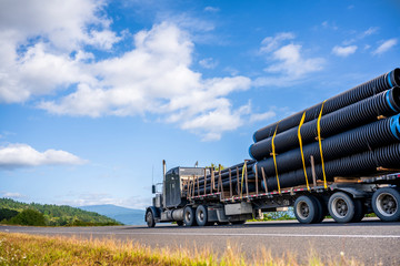 Black powerful big rig semi truck transporting plastic pipes fastened on step down semi trailer running on the road Wall mural