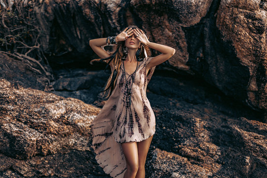 beautiful young woman in stylish boho dress closing her eyes with hands. boho style model posing outdoors at sunset