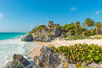 The Caribbean Sea with turquoise waters and white sand beach as a backdrop for the Tulum Maya ruins, Mexico.