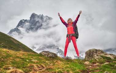 Happy hiking woman with backpack standing with rise up hands in mountain area.