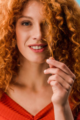portrait of beautiful woman holding red curly hair