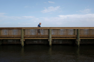 A man walks along a pier in Indian River at Parrish Park ahead of the arrival of Hurricane Dorian in Titusville