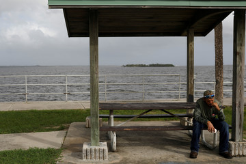 A man smokes a cigarrette at Parrish Park ahead of the arrival of Hurricane Dorian in Titusville