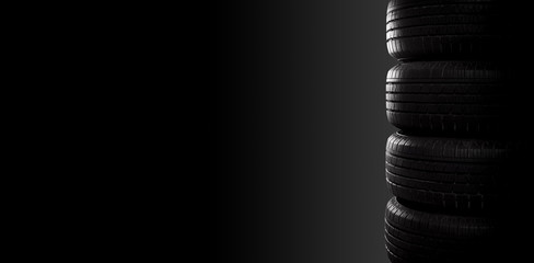 Studio shot of four black car tires on black background with copy space. Wall mural