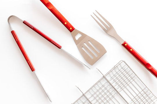 Grid, tongs, fork, spatula for barbecue and grill on white background top view