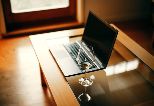 Desk Laptop with wineglass, home office, work in the evenings