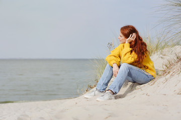 Pensive young woman sitting relaxing on a beach