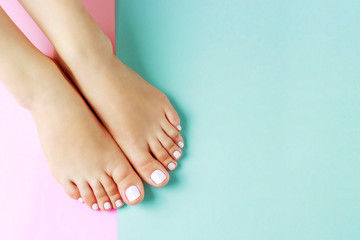 Photo sur Plexiglas Pedicure Female legs with white pedicure on pink and blue background, top view