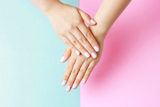 Female hands with white manicure on a pink and blue background, top view