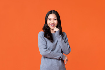 Happy Asian woman smiling with hand on chin