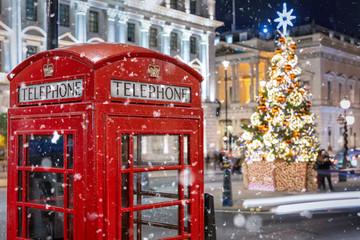 Rote Telefonzelle in London vor einem beleuchtetem Weihnachtsbaum zur Adventszeit, Großbritannien