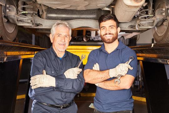 KFZ Meister und Mechatroniker Lehrling vor Auto