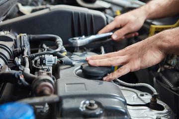 Hand mit Werkzeug am Auto Motor bei Inspektion