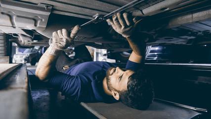 Mechatroniker bei Unterboden Reparatur am Auto