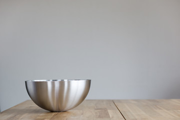 Large metal vegetable dish on wooden table with space for your design and text.
