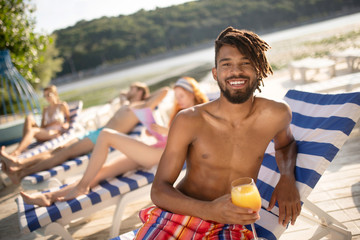 Bearded African-American man relaxing near river with friends