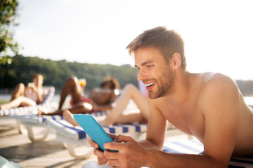 Handsome dark-haired man smiling while watching video on tablet