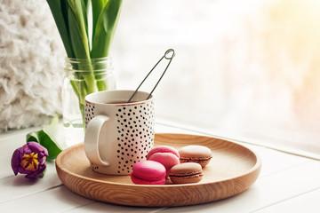 Aluminium Prints Macarons A cup of tea, sweet dessert macarons and purple tulips on a window sill.
