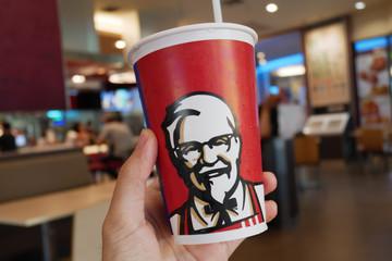 Bangkok, Thailand - May 29, 2019: Customer holding KFC cup in KFC restaurant.
