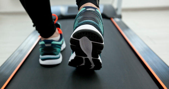The woman's legs in new sneakers on the treadmill
