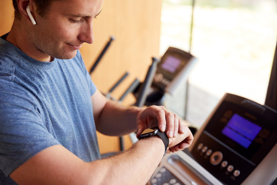 Man Exercising On Treadmill At Home Wearing Wireless Earphones Checking Smart Watch
