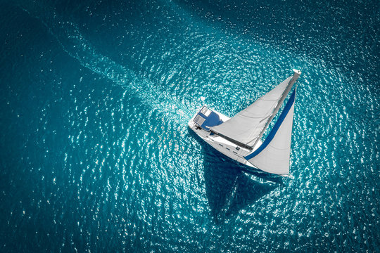 Regatta sailing ship yachts with white sails at opened sea. Aerial view of sailboat in windy condition