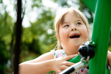 A portrait of trisomie 21 child girl outside having fun on a park