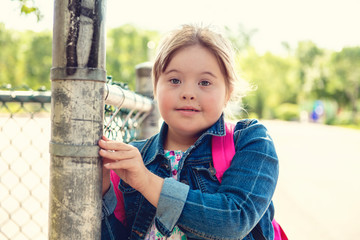 A portrait of trisomie 21 child girl outside on a school playground
