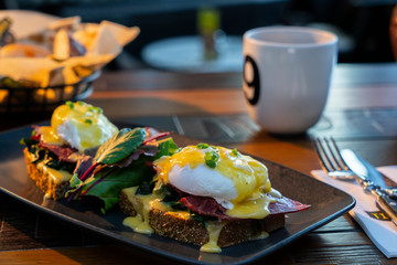 Breakfast with poached egg on toast and coffee and it served on wooden table