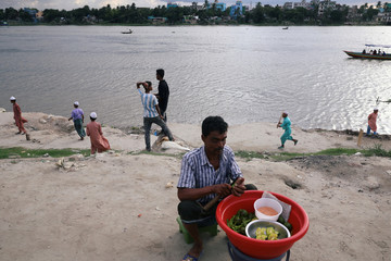 Children play cricket in the afternoon at the bank of the Buriganga river in Dhaka