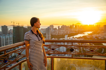 Young woman looks at view of Sanya city with river at sunset light, Hainan province, China
