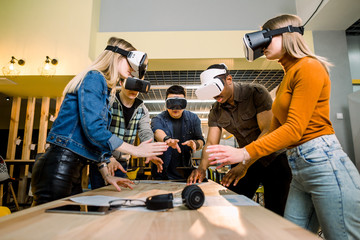 Business people using virtual reality goggles during meeting. Team of multiethnical developers testing virtual reality headset and discussing new ideas to improve the visual experience.