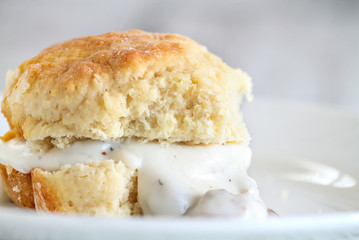 American biscuits from scratch served with thick white sausage gravy. Selective focus against white background.