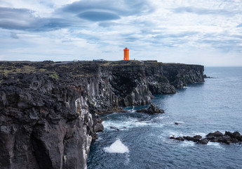 Lighthouse on the rocks in the Iceland. High rocks and lighthouse at the day time. Natural...