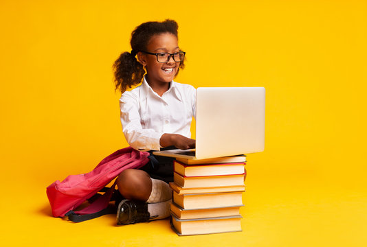 African American Schoolgirl Sitting At Laptop Doing Homework, Studio Shot