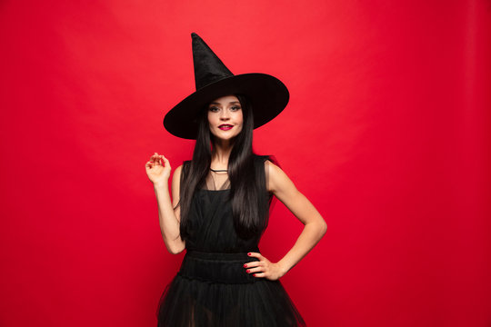 Young brunette woman in black hat and costume on red background. Attractive caucasian female model. Halloween, black friday, cyber monday, sales, autumn concept. Copyspace. Pointing up.