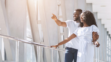 Excited african couple looking at window in airport Fototapete