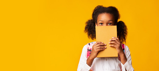 African American Schoolgirl Covering Face With Book, Yellow Background