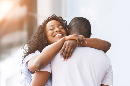 Cheerful african girl embracing with her lover outdoor