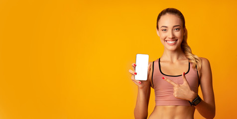 Woman Pointing Finger At Smartphone Blank Screen, Yellow Background, Mockup