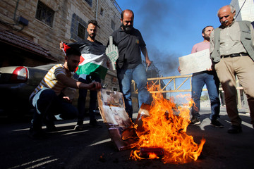 Palestinians burn pictures depicting Israeli Prime Minister Benjamin Netanyahu during a protest against the planned visit of Netanyahu to the divided town of Hebron, in the Israeli-occupied West Bank